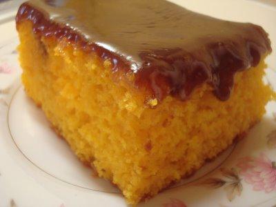 Pedaço de bolo de cenoura com cobertura de chocolate.
