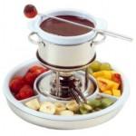 Réchaud com fondue de chocolate e frutas em volta.