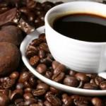 Trufa de cafe ao lado de uma xicara de cafe e grãos de café.
